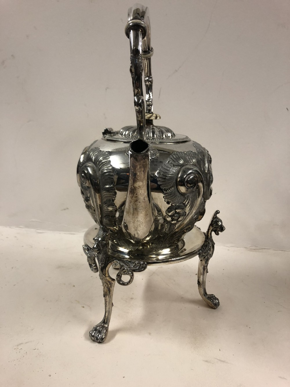 a silver plated kettle on stand