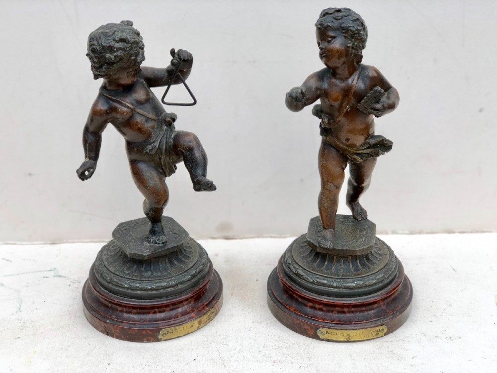 pair of spelter putti playing instruments